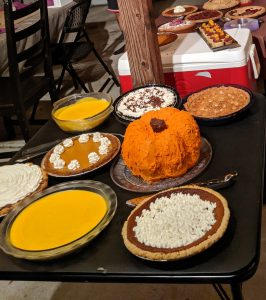 a Thanksgiving spread of many pies and a pumpkin shaped cake