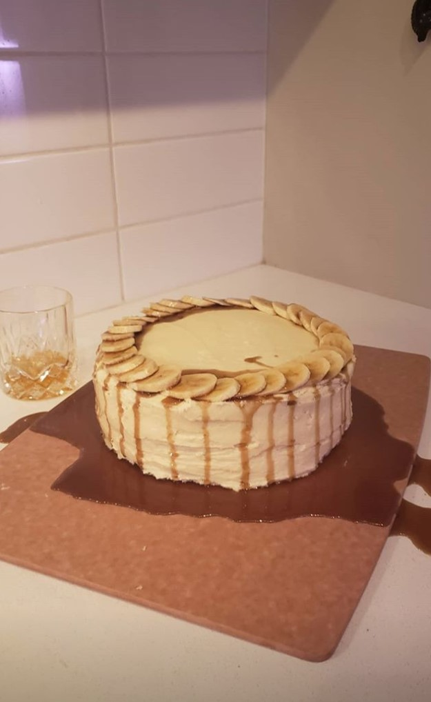 a round cake with banana slices around the perimeter with caramel drizzled along the side
