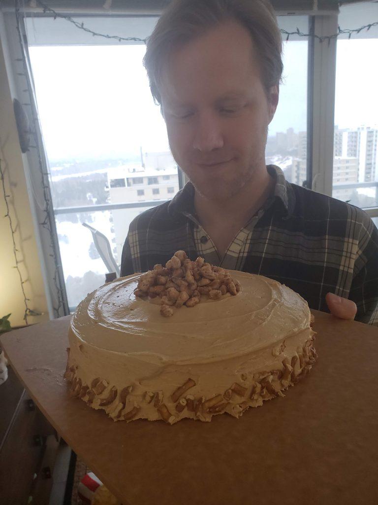 a man holding a pretzel peanut butter cake