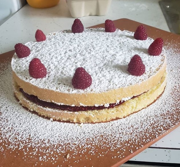 a cake on a wood board with powdered sugar sprinkled on it and raspberries arranged around the perimeter