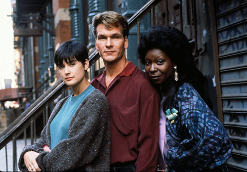 A promotional photo for the film 'Ghost' (1990). Whoopi Goldberg, Patrick Swayze, and Demi Moore all pose together on teh street.
