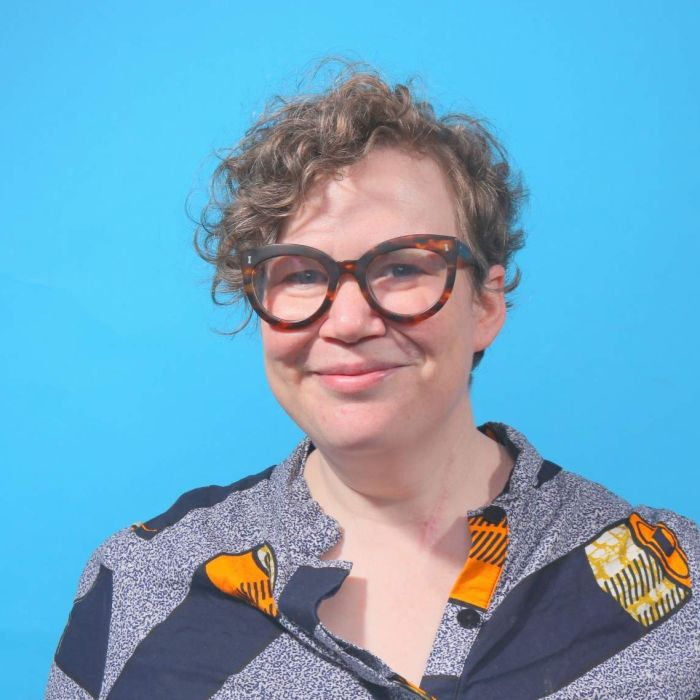 A woman wearing glasses in front of a blue background