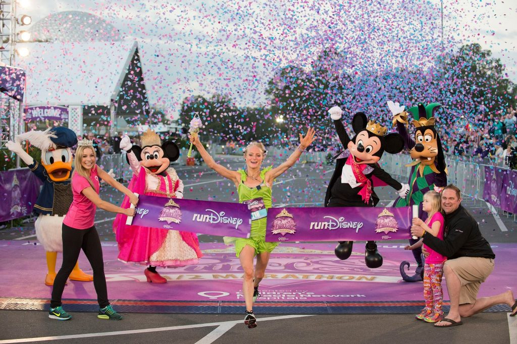 a woman crossing a finish line with confetti in the air. She is wearing a Tinkerbell costume. Costumed Donald Duck, Minnie Moue, Mickey Mouse, and Goofy are surrounding her.