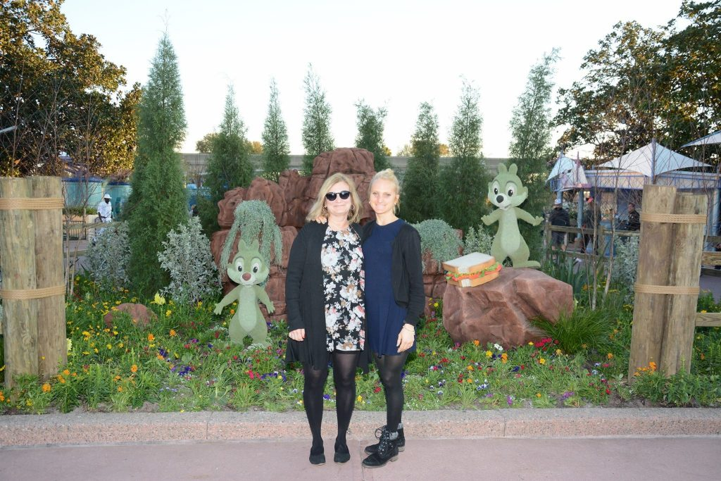 two white women with blond hair standing in front of a floral display, with green shrub-like sculptures of Chip & Dale