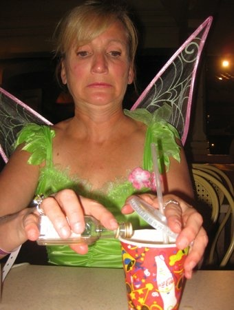 a woman wearing a Tinkerbell costume pouring a tiny vodka bottle into a drink