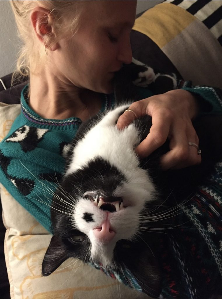 a woman holding her cat. The cat is upside down with fangs out.