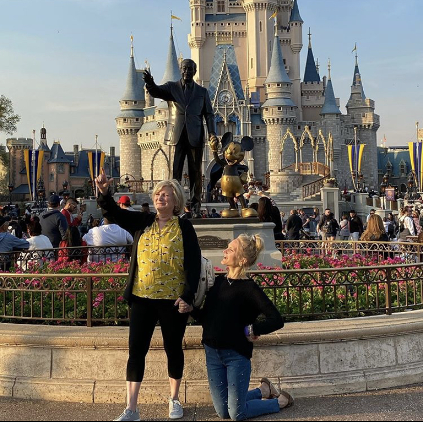 two women posed in front of a statue of Walt Disney and Mickey Mouse. The women are posed in the same style as Walt and Mickey.