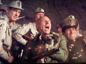 a shot from David Lynch's movie DUNE, wherein a bald man surrounded by other men in battle while also holding a pug, who happens to be looking directly into the camera