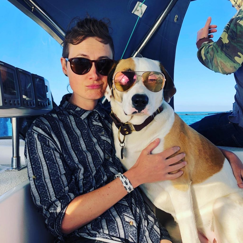 a woman wearing sunglasses posing on a boat with a dog wearing sunglasses
