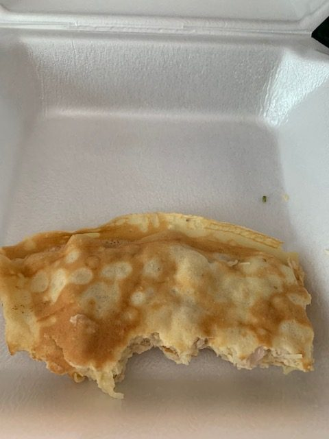 a crepe in a styrofoam container with a couple bite marks taken out of it