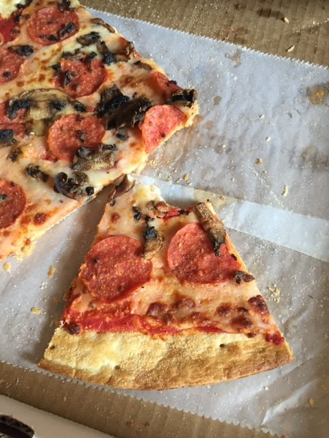 a slice of pizza with bites taken out of it