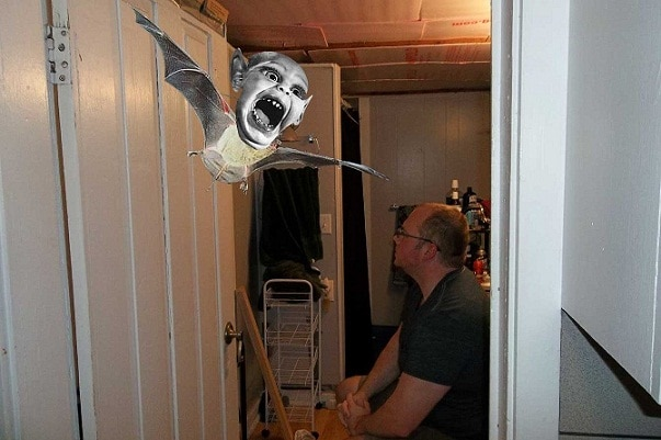 a man in a dilapidated bathroom preparing to fight a creature photoshopped in. the creature has the face of Bat Boy from the Weekly World News