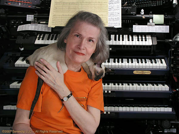 a woman in front of a set of synths with a cat draped over her shoulders