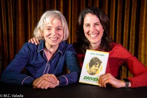 Julie Heldman and Erin Foley on stage at the angel city brewery as Erin holds Julie's book.