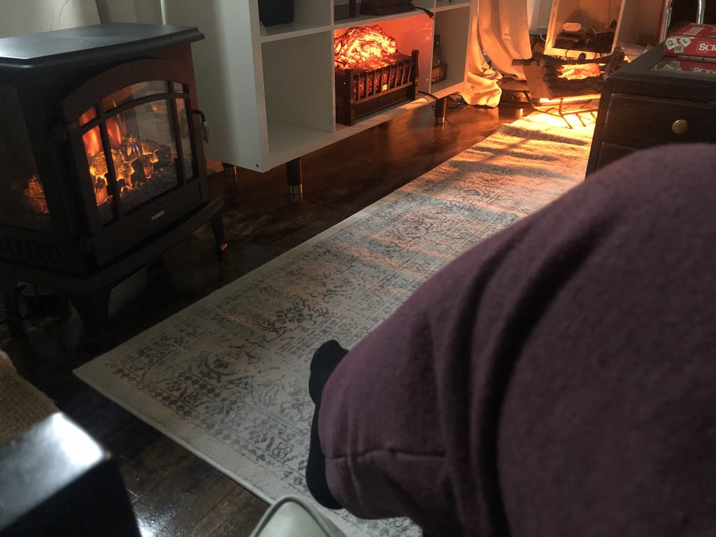 a person's sweatpanted leg in the foreground, with 3 different fireplace inserts in the background