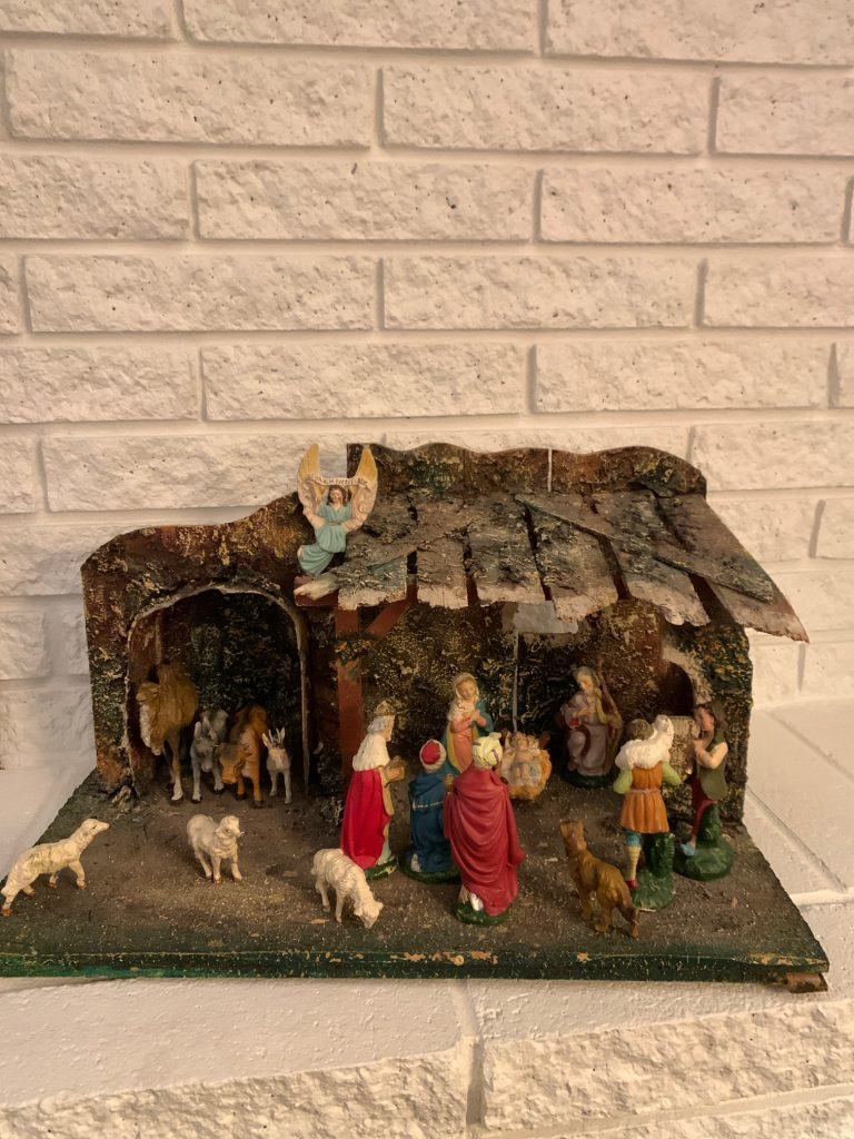 a christmas nativity scene in a home against a white brick wall
