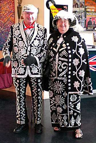 two people with black outfits covered in pearls