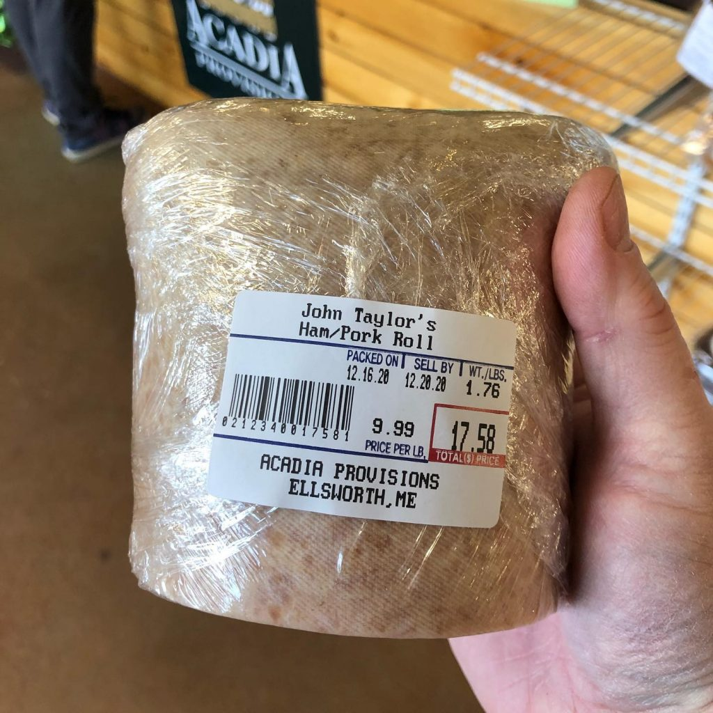 a human adult hand holding a deli-wrapped chunk of Taylor Ham/Pork Roll