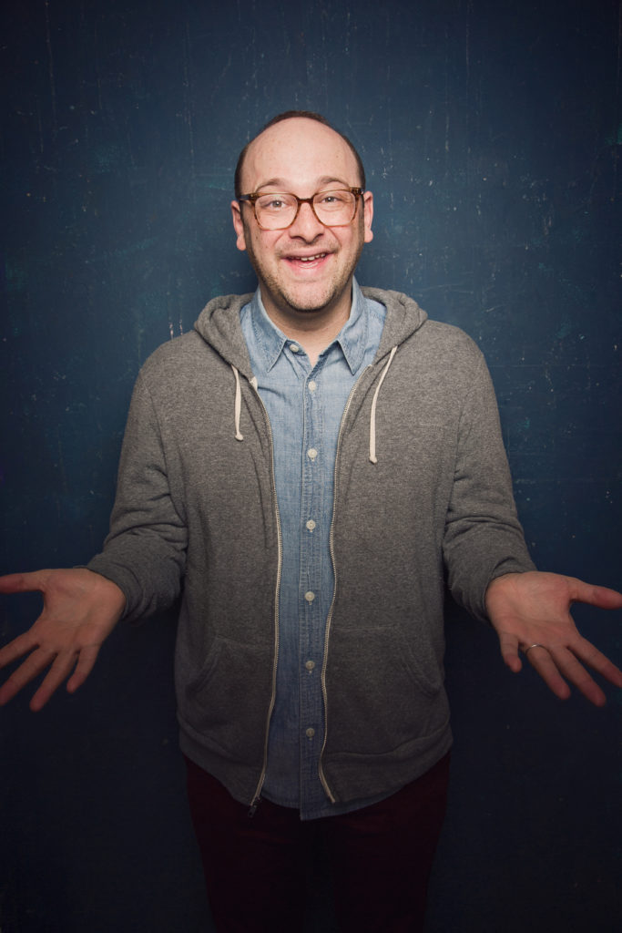 "Josh Gondelman in front of a blue background, smiling and holding his hands out as if to say ""hey there!"""