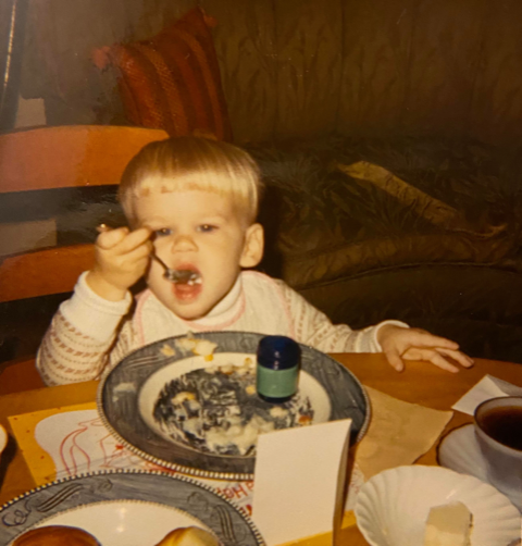 an old photo of a blond child with a bowlcut, finishing his Thanksgiving dinner with an open and empty container of Vicks Vaporub next to his plate