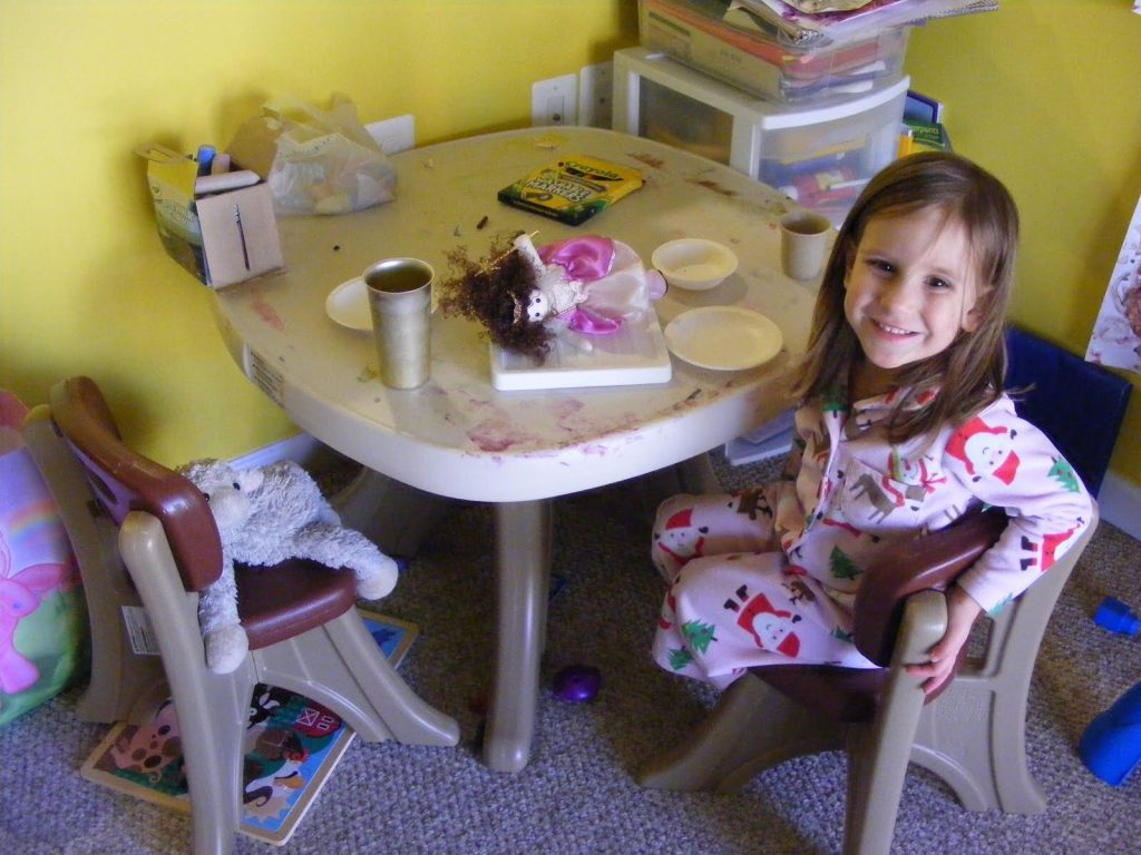 A smiling 3 year old girl sitting at a kids' sized table, with a lamb stuffy on the other chair. A fairy doll is on a platter in the middle of the table. There appears to be watery red paint smudges all over the table.