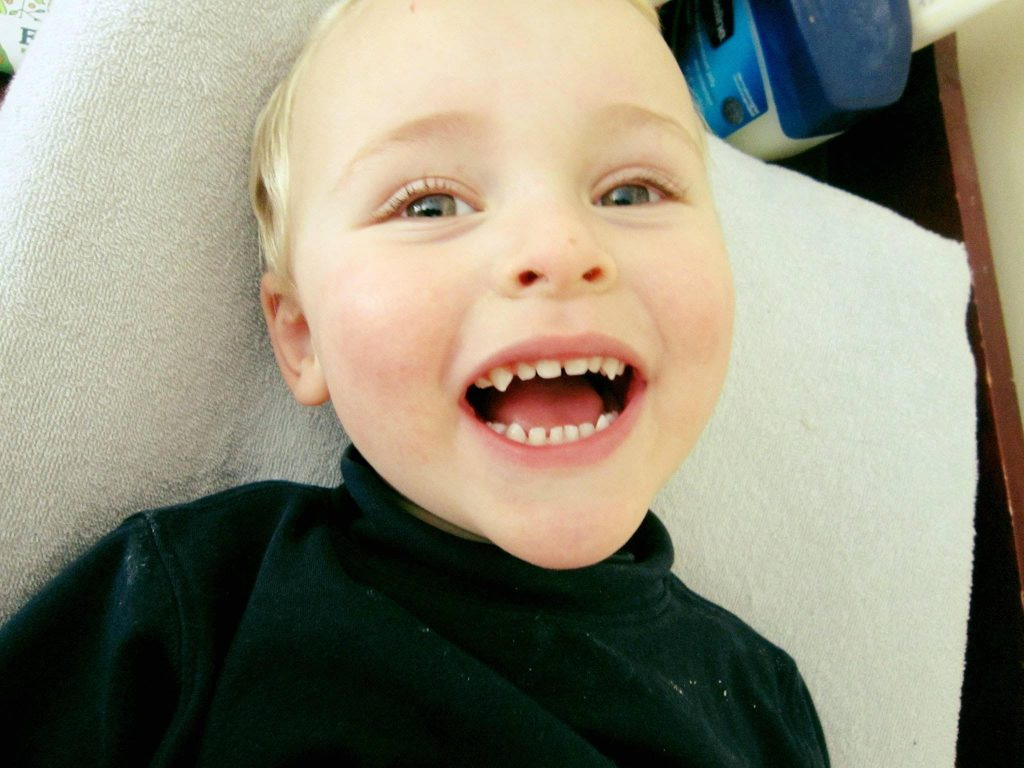 A white, blond toddler laying on a changing pad, wearing a black turtleneck shirt. He has an open mouthed smiling expression and his canine teeth are very sharp!