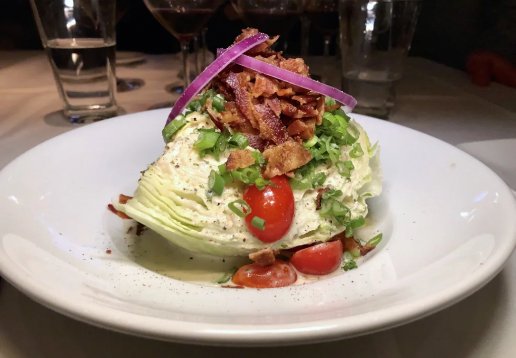 A wedge salad on a white plate in a restaurant: one wedge of iceberg lettuce topped with halved cherry tomatoes, blue cheese dressing, green onion slices, bacon pieces, and red onion slices on top