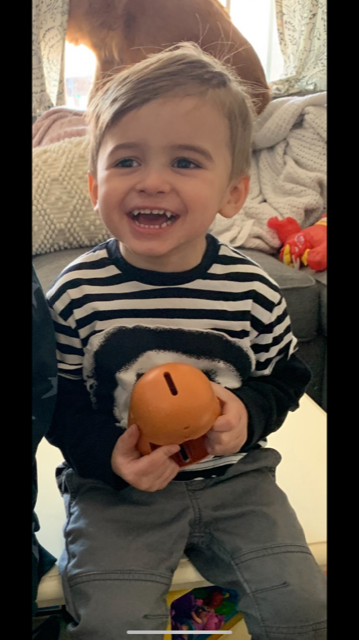 A toddler holding a potato head toy and smiling. He has sharp canine teeth that make him look like a vampire