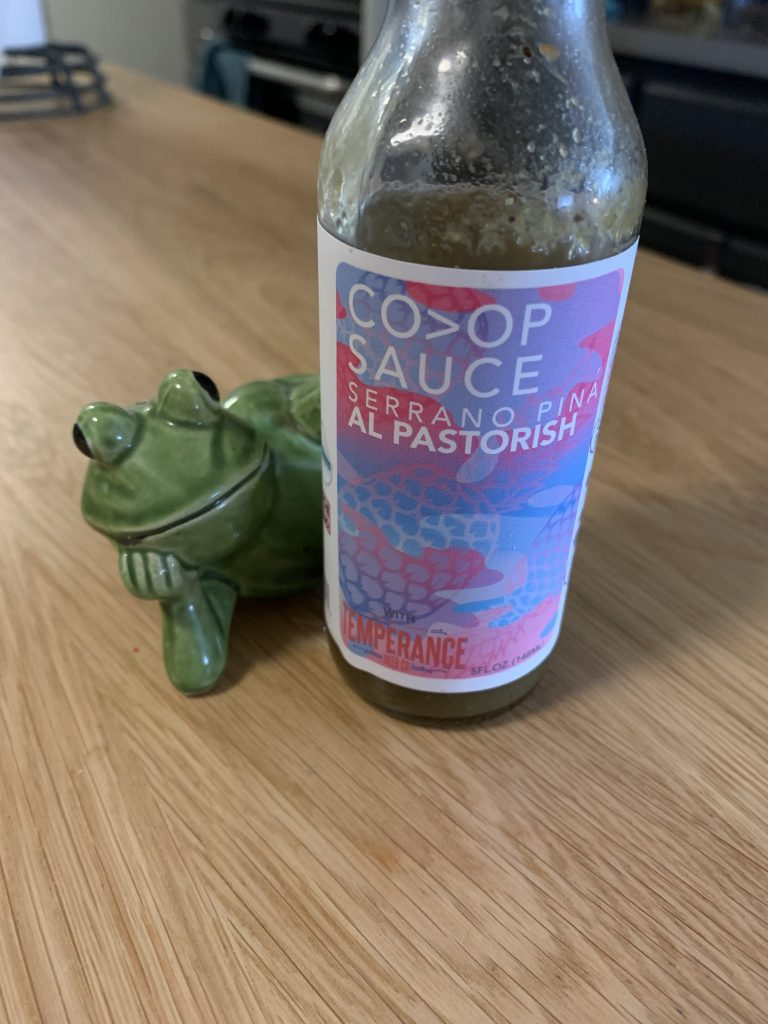 A bottle of Co>Op Al Pastorish Hot Sauce, with a green ceramic from posed behind it. The frog figurine is posed on its side with a hand under the chin.