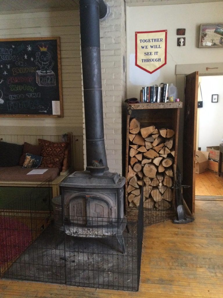 A 1970s cast iron wood burning stove, in a home. Behind and to the right is a wood pile.