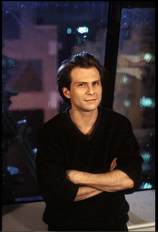 A white man (Christian Slater) with a 90s style floppy hairdo standing with his arms crossed and vaguely smirking.