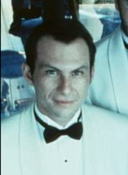 Christian Slater: A white man with slicked back hair, smirking, and wearing a white tuxedo and black bowtie