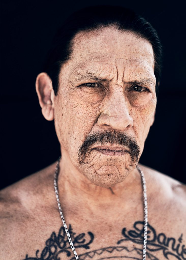 A Mexican American man with a handlebar mustache and dark hair pulled back in a ponytail. He has a serious expression on his face and is shirtless, wearing a chain necklace around his neck.