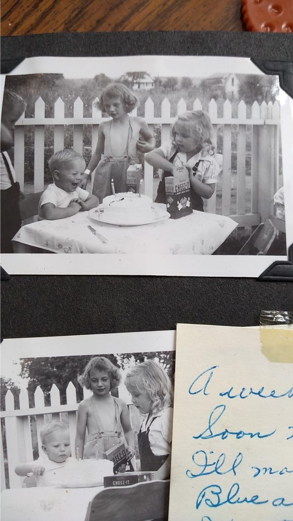 A photo of two old black and white photos in a scrapbook. The top photo shows 4 young kids around a table outside. One of the children is seated, and smiling big in front of his birthday cake. On the table are also a box of Cheez-Its. One of the older kids is shirtless with suspenders and pants. The bottom photo is another angle of the same scene. There is part of a handwritten note in the bottom right corner.