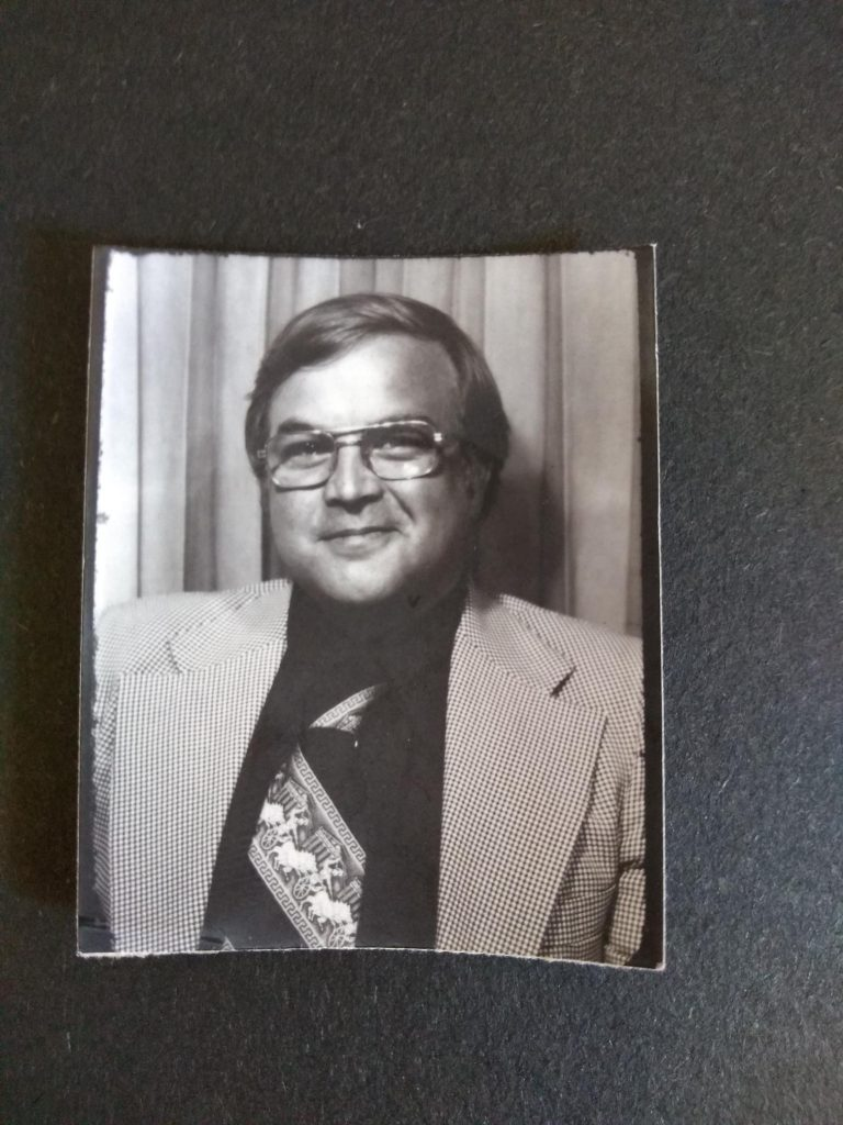 A black and white photo of a man in front of a curtain, wearing glasses, a blazer, and a wide tie