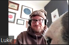 A man wearing glasses and headphones on a Zoom call with part of a dog's face in the bottom right corner of the screen.