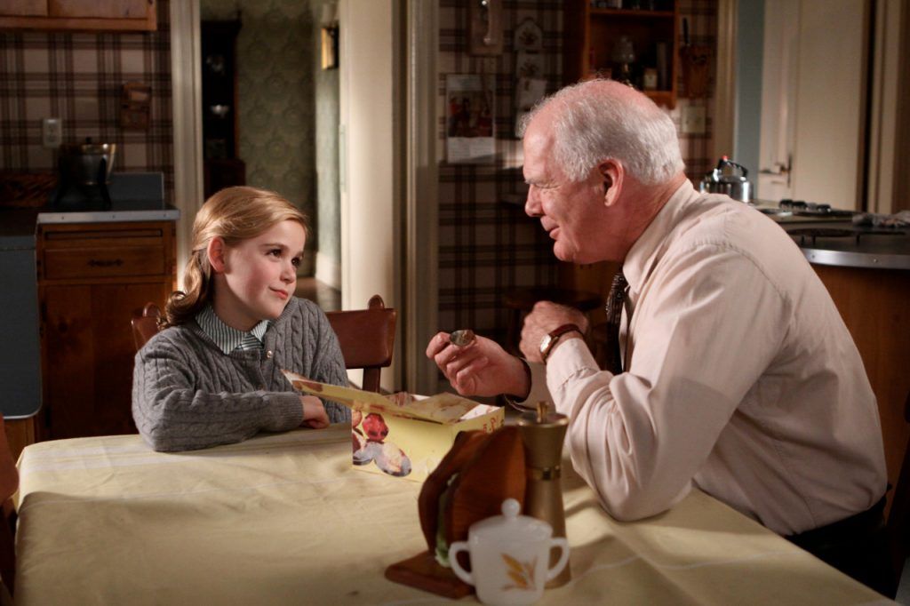 A still from Mad Men, which takes place in the 1960s. A young blond girl is sitting at a kitchen table with an older white haired man. They are sharing a carton of chocolate ice cream