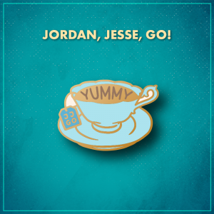"""Jordan, Jesse, Go! A fancy light blue tea cup on a light blue saucer, filled with tea. The tea has the word """"yummy"""" written on it, and a blue tea bag hangs down the left side with the letters """"JJGO"""" on it."""
