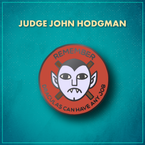 """Judge John Hodgman. A red circle with the pale face of a frowning vampire with a widow's peak and pointy ears in the middle. Behind the vampire are two crossed brown sticks, and the word """"Remember"""" arches along the top of the pin, with """"Draculas can have any job"""" arching along the bottom of the pin."""