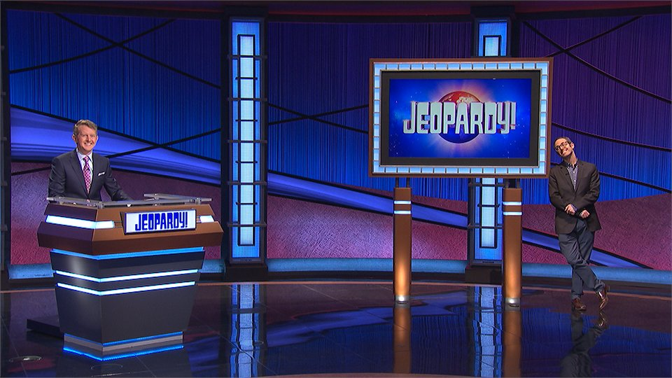 A photo of the Jeopardy tv show stage, with guest host Ken Jennings at the host podium. Elliott Kalan is to the right of the stage posing with a screen showing the show logo.