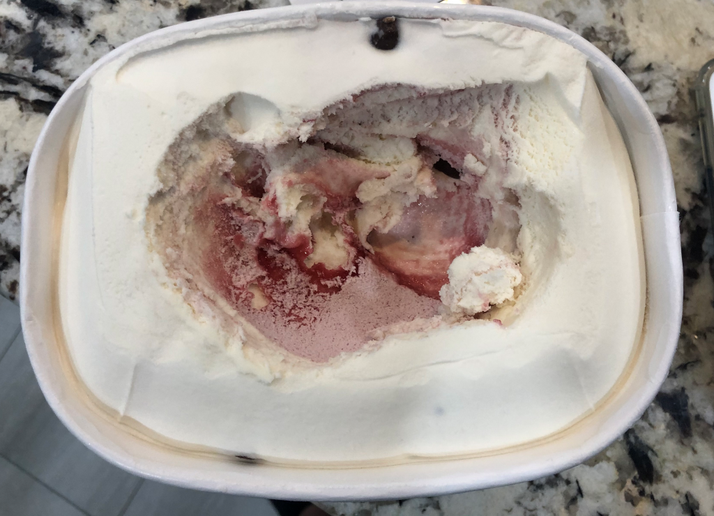 A container of white chocolate raspberry ice cream. Only the center is scooped and the raspberry swirl is visible. The ice cream around the scooped center is pristine white chocolate.