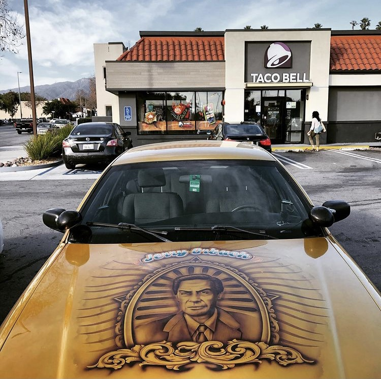 A gold car, from the front, with a Jerry Orbach illustration airbrushed on the hood.