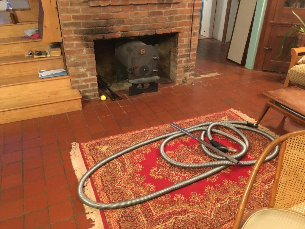 A long silver vacuum tube haphazardly strewn on a living room rug.