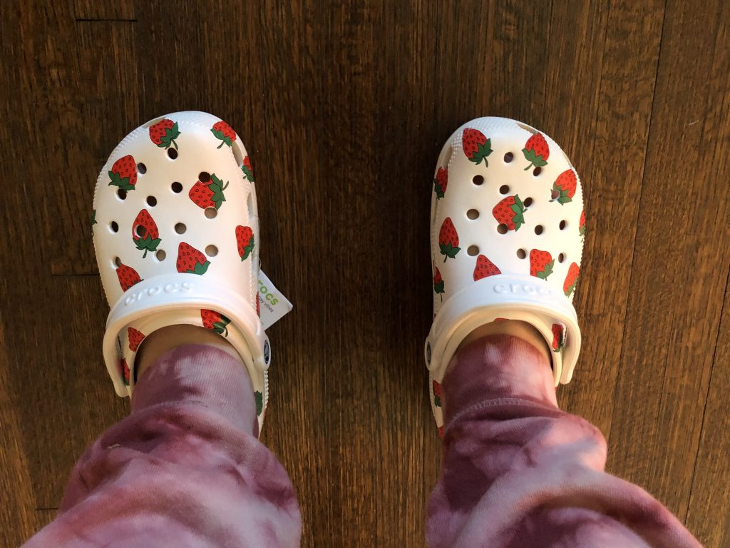 An overhead view of a person's legs and feet. This person is wearing pink tie dyed sweatpants and white Crocs with strawberries printed on them.