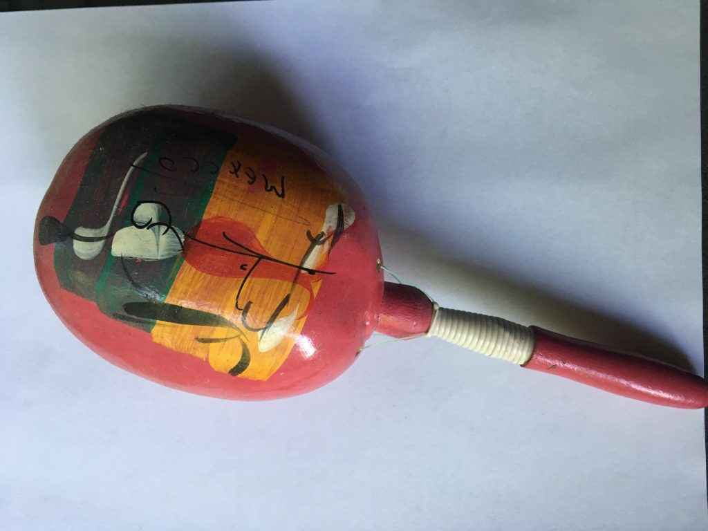 A red wooden, seemingly hand painted maraca. There is a green, orange and white design painted on it.