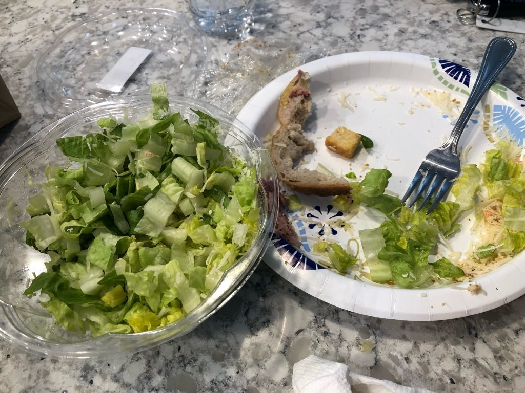 A clear bowl of chopped romaine lettuce next to a paper plate. On the paper plate is a fork with a mostly eaten undressed salad.