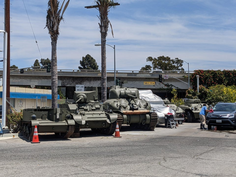 tanks parked on the edge of a gas station in a city near a freeway overpass