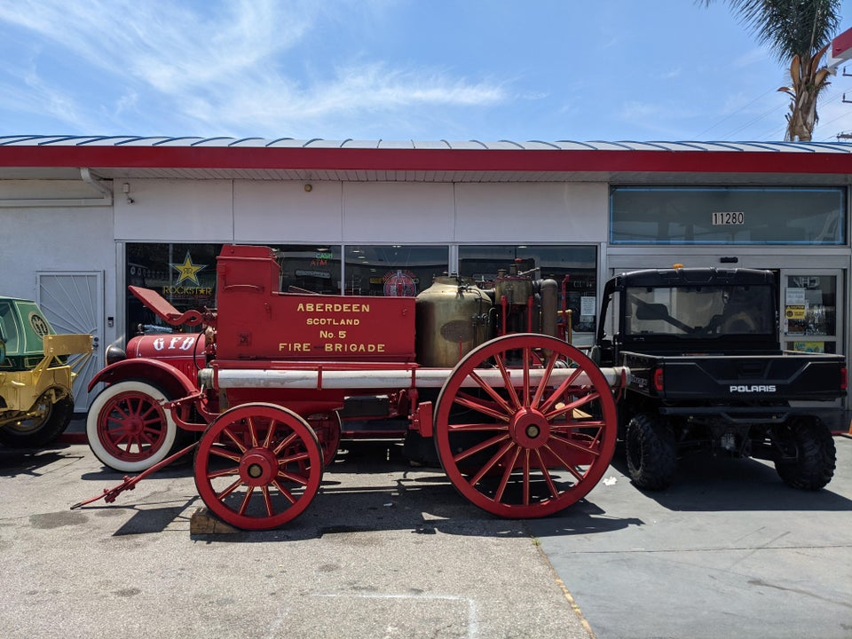 A very old style fire engine parked at a gas station