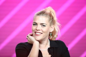 Busy Philipps sitting in front of a pink backdrop