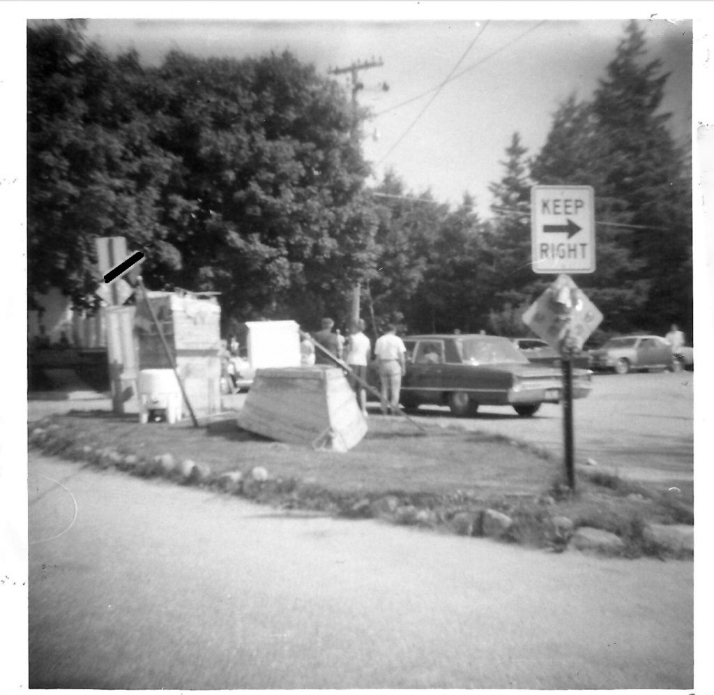 Black and White photo of a large item trash pile on the side of a road. A small boat is part of the pile.
